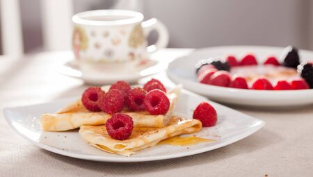 breakfast of tasty pancakes with fresh raspberries on table