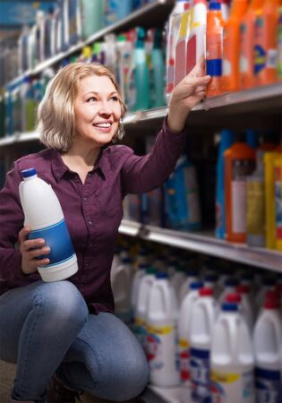 smiling female with selecting fabric conditioner in household store