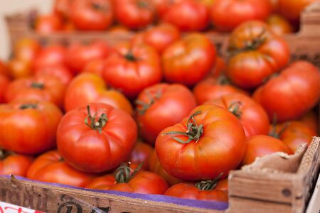 red fresh tomatoes on branch in wicker baskets on counter