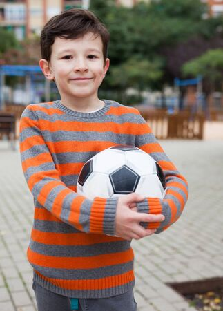 boy holding soccer ball outdoors in autumn