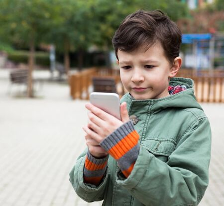 modern boy holding smartphone outdoors in autumn