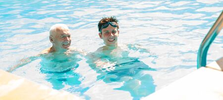 grandfather and grandson communicate in swimming pool