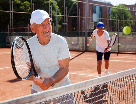 grandfather and grandson playing tennis court