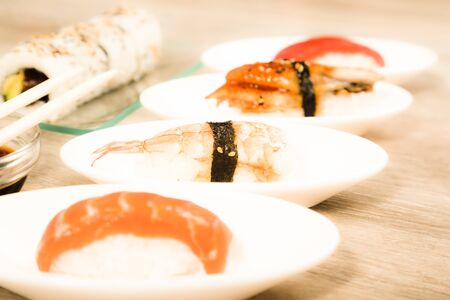 four kinds japanese Nigirisushi on oval saucers and Uramaki. focus on ebi