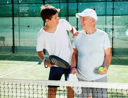 Cheerful positive smiling older man and a young man talking on court playing paddle Stock fotó