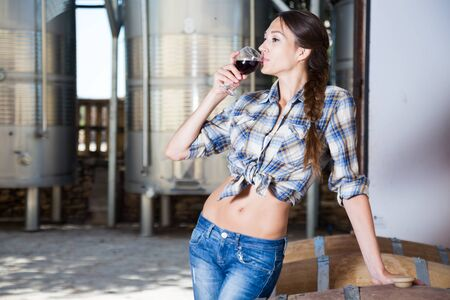 beautiful woman is tasting wine at Italian wine factory