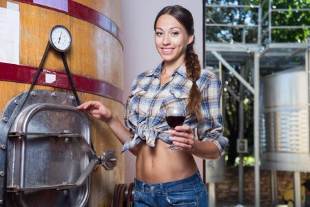 pretty woman checks wine at factory in France