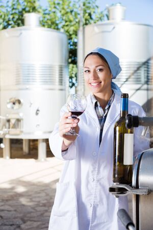 girl specialist in white coat examines glass of wine on the background of barrels for fermentation