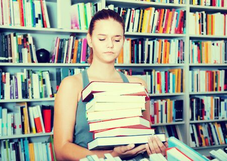 brunete girl chooses a book in university library