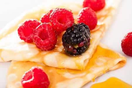 delicious pancakes with raspberries, blackberries and honey