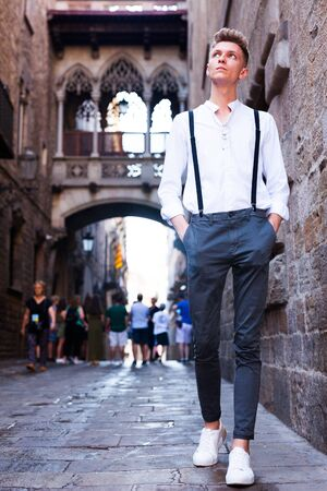 ordinary young European guy in shirt and trousers with suspenders walking around city