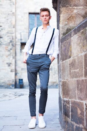 ordinary young European guy in shirt and trousers with suspenders walking around city Imagens - 134482670