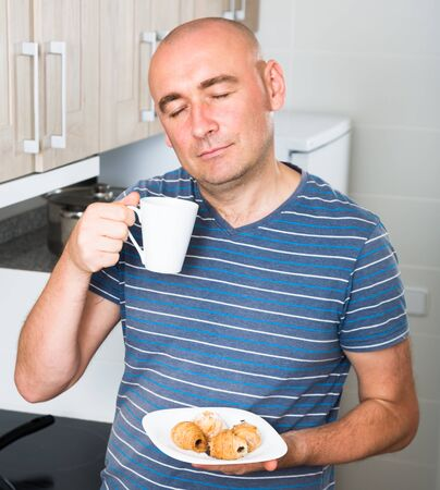 guy with eyes closed drinking coffee and croissants in the morning