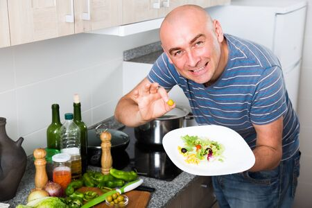 smiling man holding fingers in green olives