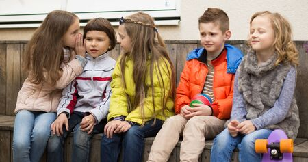 european Children on a bench playing Chinese whispers