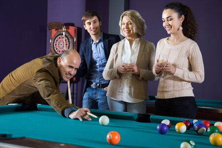 two adult couples of different generations talk in the billiard room. focus on mature man Imagens