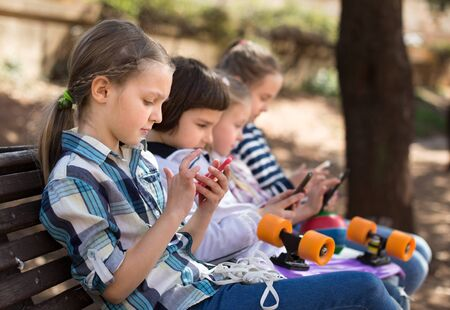 ordinary children playing with the phone on bench in park