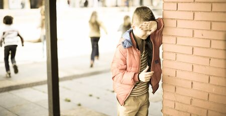 playing hide and seek. ordinary boy closed eyes his hands standing at brick wall