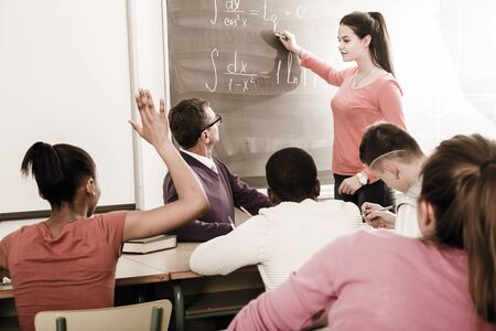 cute student girl solves task near blackboard in multi-ethnic classroom Reklamní fotografie