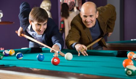 Two men playing billiards. focus on ball