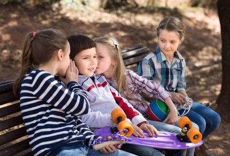 Happy girl and boy sitting in park on bench in spring and whispering. focus on girl Imagens - 134482541