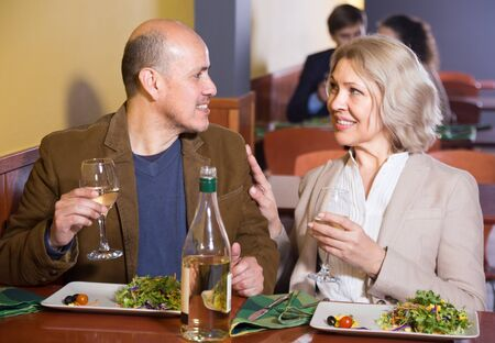 Positive  smiling mature couple having dinner at restaurant