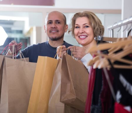 happy mature couple with shopping bags in their hands in clothing shop