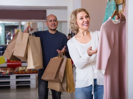 Mature couple choosing new apparel in clothing store Imagens