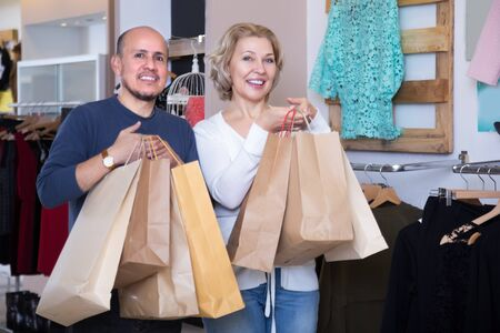 Mature couple with shopping bags in their hands in clothing shop