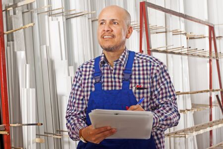 Bald worker in warehouse takes notes