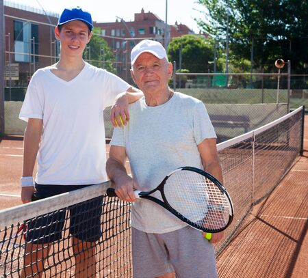 lawn tennis players of different generations posing on tennis court