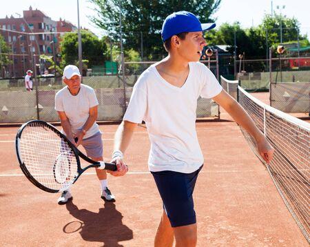 dziadek i wnuk grają na korcie tenisowym