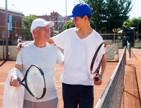 older man and young man talking on court playing tennis Imagens