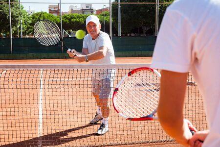 mature man playing at tennis court Imagens