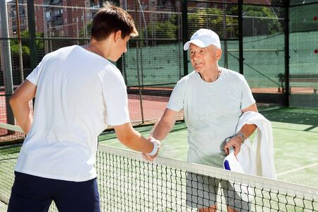 Glad cheerful  senior and young man shake hands before padel tennis match