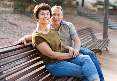 elderly man and woman embracing on park bench