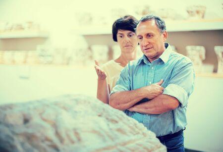 mature couple turists examines the exhibit in historical museum Imagens