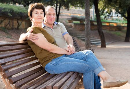 mature man with a woman sitting on bench in spring Imagens