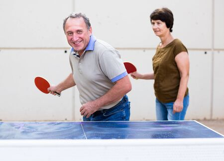 mature couple playing table tennis outdoors