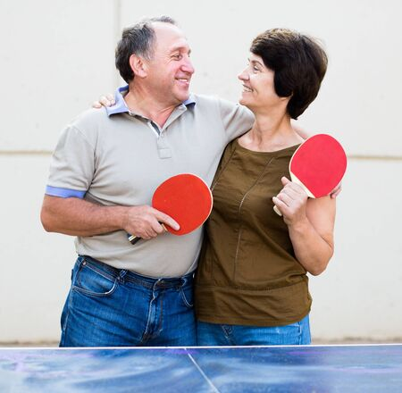portrait of elderly posing couple with rackets for table tennis Imagens