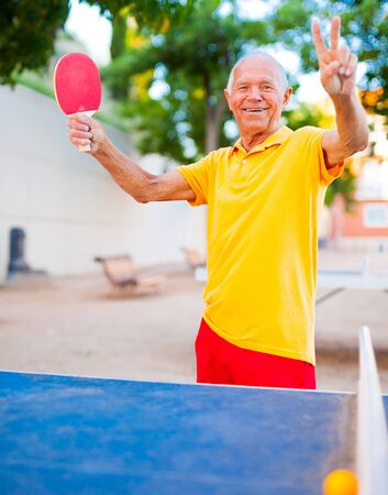 portrait of senior with rackets for table tennis showing victory