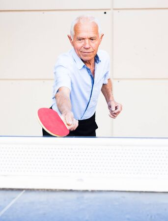 portrait of elderly man with rackets for table tennis
