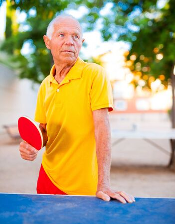 Happy mature man posing with rackets at table tennis
