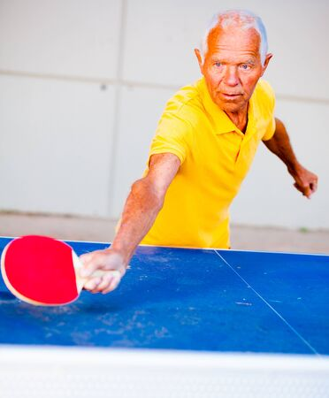 mature man in yellow Tshirt playing table tennis outdoors Imagens
