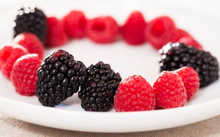 fresh raspberries and blackberries laid out on a white plate in circle