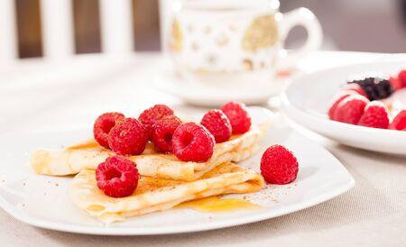 breakfast of tasty pancakes with fresh raspberries on table