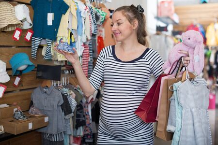 pregnant woman in striped tunic chooses shoes for the baby in boutique Imagens