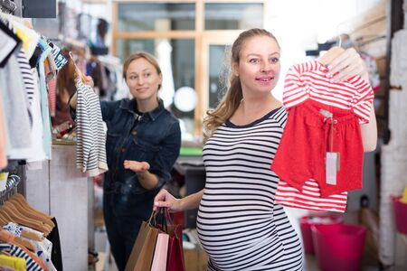 expectant mother in striped tunic chooses clothes for girl in boutique Imagens