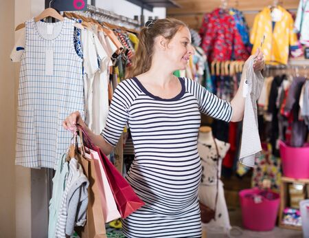 expectant mother In striped tunic shopping Dress in clothing store for babies