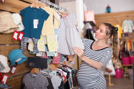 nice Pregnant woman examines a dress for a child in a store